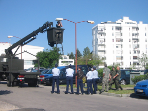 A bunch of people watching one man repairing a street light